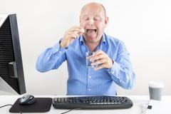 Geschäftsmann, der Pillen für Kopfschmerzen einnimmt Stockbilder