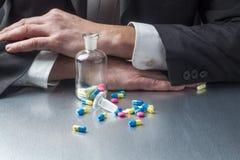 Geschäftsmann, der Pillen und Drogen für das Gegenüberstellen von Arbeitsplänen nimmt Stockfoto