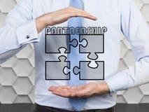 Geschäftsmann, der Puzzlespiel vier hält Lizenzfreie Stockbilder