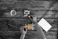 Geschäftsmann, der Puzzlespiele bei der Arbeit löst Stockfoto