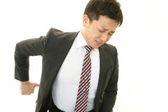 Geschäftsmann, der Rückenschmerzen hat Stockfoto