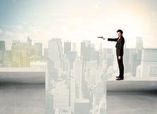 Geschäftsmann, der am Rand der Dachspitze steht Stockfotos