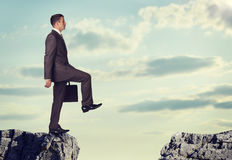 Geschäftsmann, der am Rand des Felsenabstandes steht Lizenzfreie Stockfotos