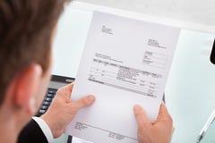 Geschäftsmann, der Rechnungspapier hält Stockbild