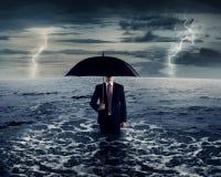 Geschäftsmann, der Regenschirm auf dem Meer hält Stockbild