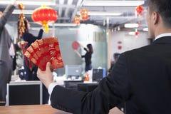 Geschäftsmann, der rote Umschläge halten und Mitarbeiter, die Dekorationen für chinesisches neues Jahr hängen stockbild