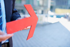 Geschäftsmann, der roten Pfeil anhält Lizenzfreies Stockfoto