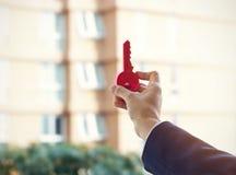 Geschäftsmann, der roten Schlüssel auf Immobilienhintergrund hält, um Ziel zu erreichen Stockfoto