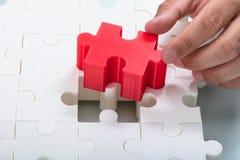 Geschäftsmann, der rotes Stück in weiße Puzzlen anschließt lizenzfreies stockfoto