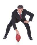 Geschäftsmann, der Rugby spielt Stockfoto