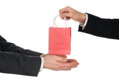 Geschäftsmann, der Säckchen gibt stockfoto