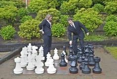 Geschäftsmann, der Schachzug im Garten macht Lizenzfreies Stockfoto