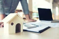 Geschäftsmann, der schaut, um eine Hausversicherungspolitik auf Wohnungsbaudarlehen zu unterzeichnen Stockbild