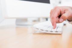 Geschäftsmann, der Schlüssel auf Tastatur drückt Lizenzfreie Stockbilder