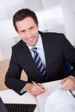 Geschäftsmann, der am Schreibtisch arbeitet Lizenzfreie Stockfotos