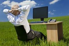 Geschäftsmann, der am Schreibtisch auf dem grünen Gebiet sich entspannt Lizenzfreies Stockbild