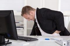 Geschäftsmann, der am Schreibtisch hat die Schmerz an der Rückseite, an den Nieren oder am musc sitzt lizenzfreie stockbilder