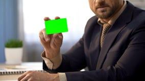 Geschäftsmann, der am Schreibtisch im Büro, farbige Karte des Grüns zeigend, Bankdienstleistungen sitzt stockfoto