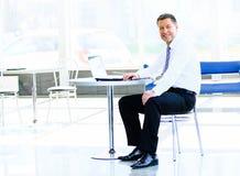 Geschäftsmann, der am Schreibtisch im Büro sitzt Stockbild