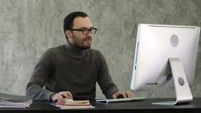 Geschäftsmann, der am Schreibtisch im Büro sitzt und auf dem Computer woking lizenzfreie stockfotos