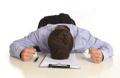 Geschäftsmann, der am Schreibtisch mit den Händen auf seinem Kopfschreien verwüstet und frustriert sitzt lizenzfreies stockbild