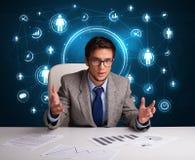 Geschäftsmann, der am Schreibtisch mit Ikonen des Sozialen Netzes sitzt Stockfotos