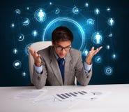 Geschäftsmann, der am Schreibtisch mit Ikonen des Sozialen Netzes sitzt Stockfotografie