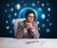 Geschäftsmann, der am Schreibtisch mit Sozialnetzikonen sitzt Lizenzfreie Stockbilder