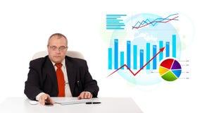 Geschäftsmann, der am Schreibtisch mit Statistiken sitzt Lizenzfreies Stockfoto