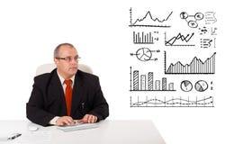 Geschäftsmann, der am Schreibtisch mit Statistiken und Diagrammen sitzt Stockbilder