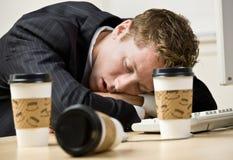 Geschäftsmann, der am Schreibtisch schläft Lizenzfreie Stockfotografie