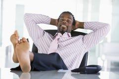 Geschäftsmann, der am Schreibtisch sich entspannt Lizenzfreie Stockfotografie