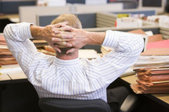 Geschäftsmann, der am Schreibtisch sich entspannt Lizenzfreies Stockfoto