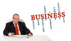 Geschäftsmann, der am Schreibtisch sitzt Stockbild
