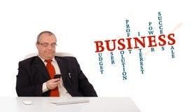 Geschäftsmann, der am Schreibtisch sitzt und ein Mobiltelefon mit busin hält Stockbilder