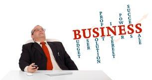 Geschäftsmann, der am Schreibtisch sitzt und ein Mobiltelefon mit busin hält Lizenzfreie Stockfotos