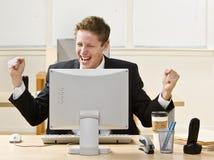 Geschäftsmann, der am Schreibtisch zujubelt Lizenzfreie Stockfotos
