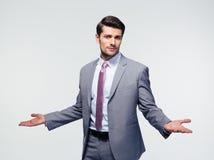 Geschäftsmann, der Schultern zuckt Stockbilder