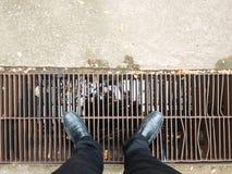 Geschäftsmann, der schwarze Hose und schwarzen die Lederschuhe unten schauen zur Entwässerung trägt Lizenzfreies Stockbild