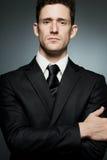 Geschäftsmann in der schwarzen Klage, die Vertrauen ausdrückt. lizenzfreie stockfotos