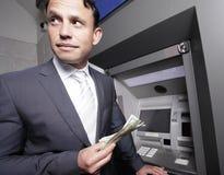 Geschäftsmann, der sein Geld anhält Lizenzfreie Stockfotos