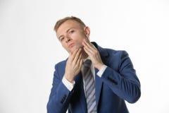 Geschäftsmann, der sein Gesicht hervorhebt Hautpflege berührt lizenzfreie stockfotografie