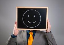 Geschäftsmann, der sein Gesicht mit einer schwarzen Anschlagtafel mit einem smiley versteckt Stockfotos