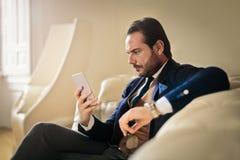 Geschäftsmann, der sein Telefon überprüft lizenzfreie stockfotos