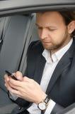 Geschäftsmann, der sein Telefon ansieht Stockfotografie