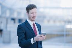 Geschäftsmann, der sein Telefon betrachtet Lizenzfreie Stockfotos