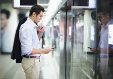 Geschäftsmann, der sein Telefon betrachtet und auf die U-Bahn in Peking wartet Lizenzfreies Stockbild