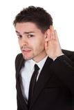 Geschäftsmann, der seine Hand zu seinem Ohr anhält Stockbilder