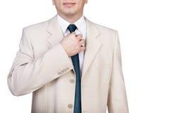 Geschäftsmann, der seine Krawatte justiert Stockbild