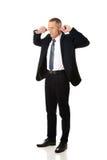 Geschäftsmann, der seine Ohren verstopft Lizenzfreies Stockfoto